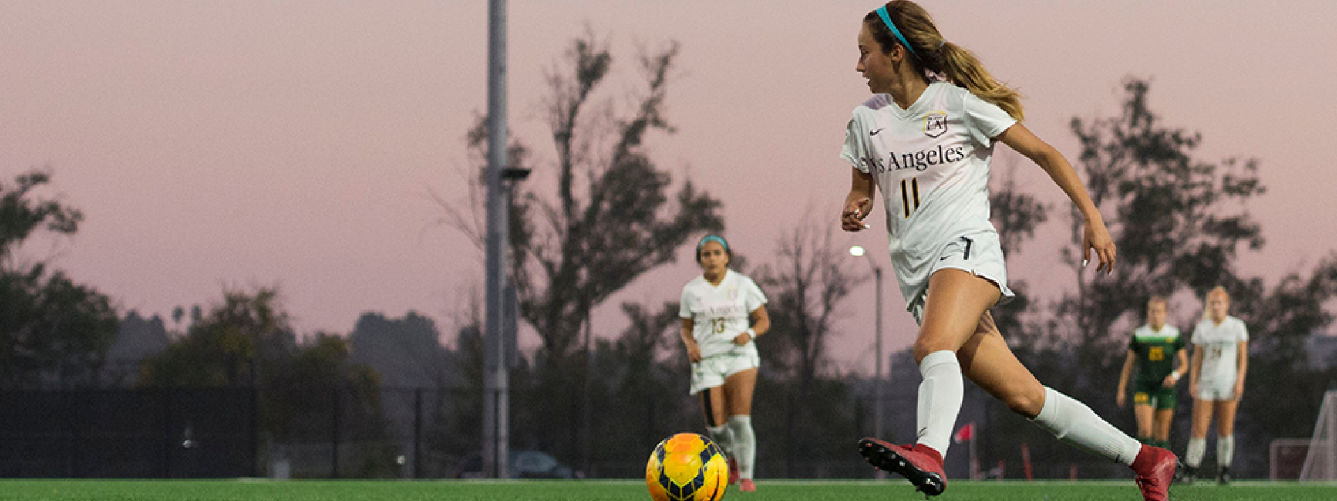 Image of a member of the  women's soccer team on the pitch at dusk, pink sky behind her.