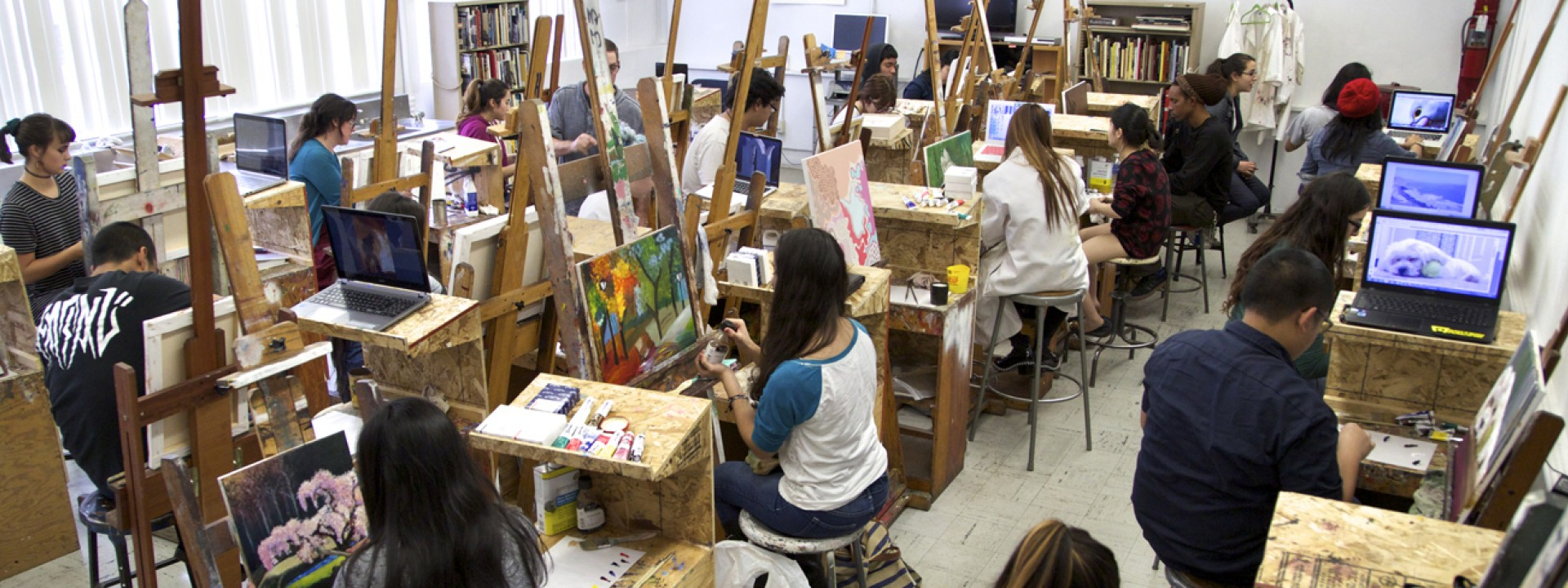 Image of students in a painting studio with easels, shot from above