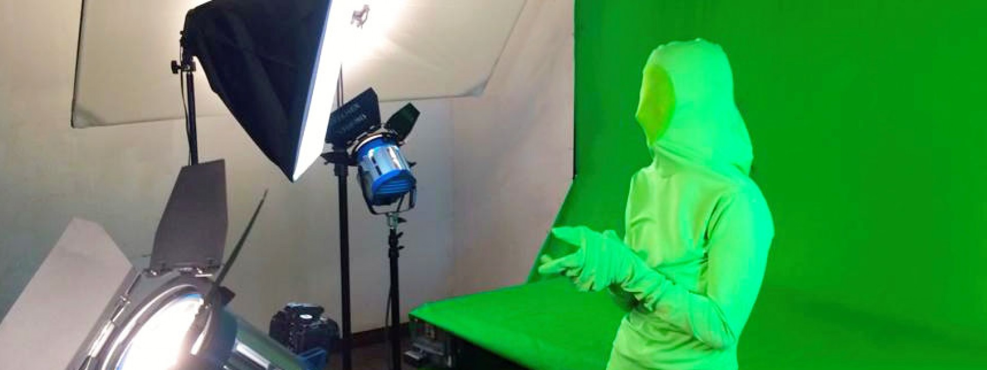 Image of a student in a green suit in front of a green screen being filmed.
