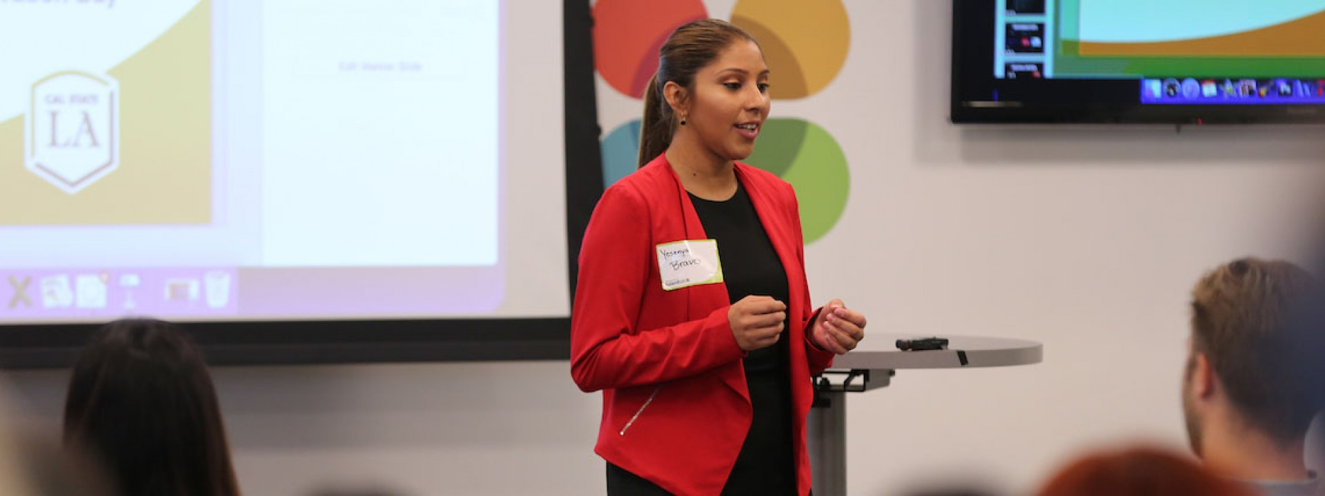 Image of a female student in a red blazer giving a presentation to her classmates.