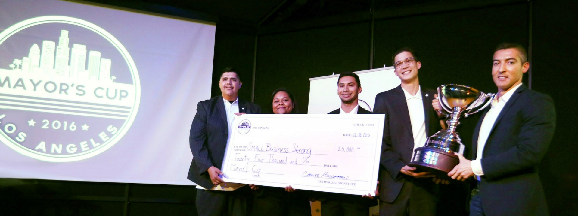 """Group of Cal State LA students in business attire on a stage holding a large check near a screen that says """"2016 Mayor's Cup"""""""