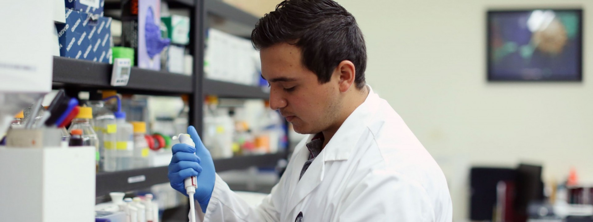 Image of the side profile of a student in a while lab coat and blue gloves using a lab instrument.