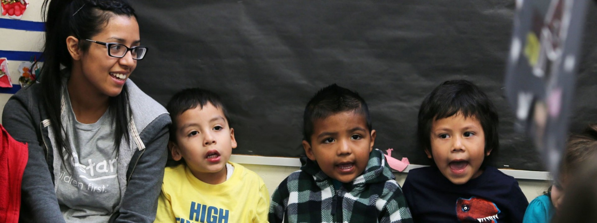 Image of a Cal State LA female student sitting next to three small children who appear to be singing.