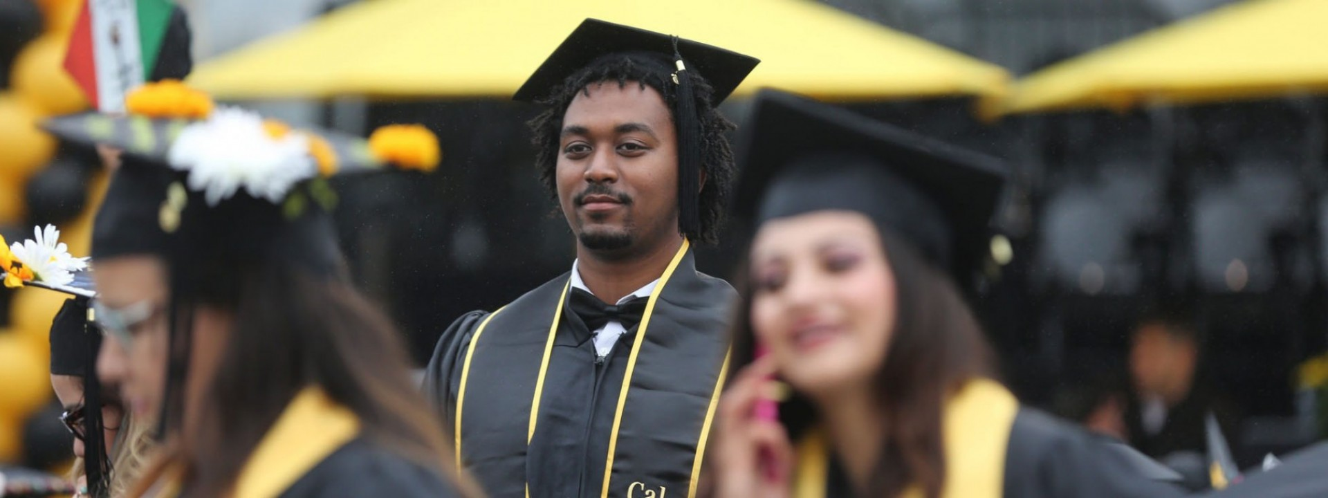 Image of a Black male student in Commencement regalia with a stoic expression on his face.