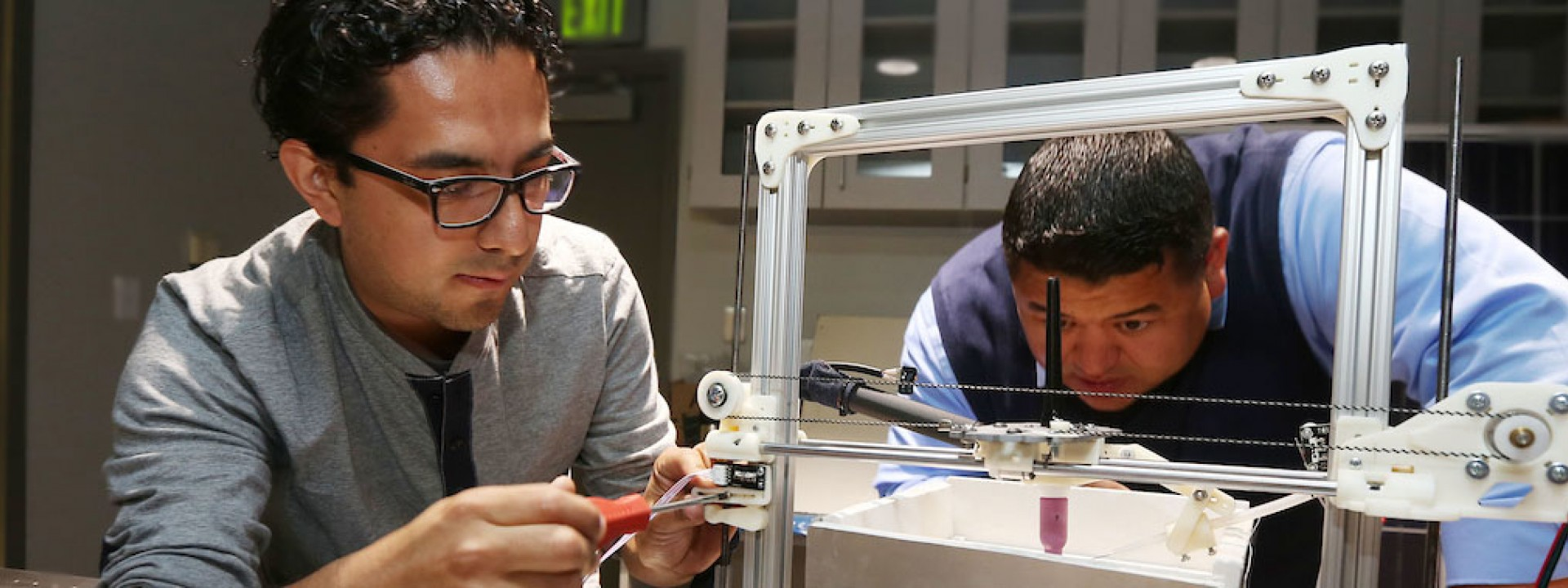 Image of two engineering students looking at a metal frame device intently.