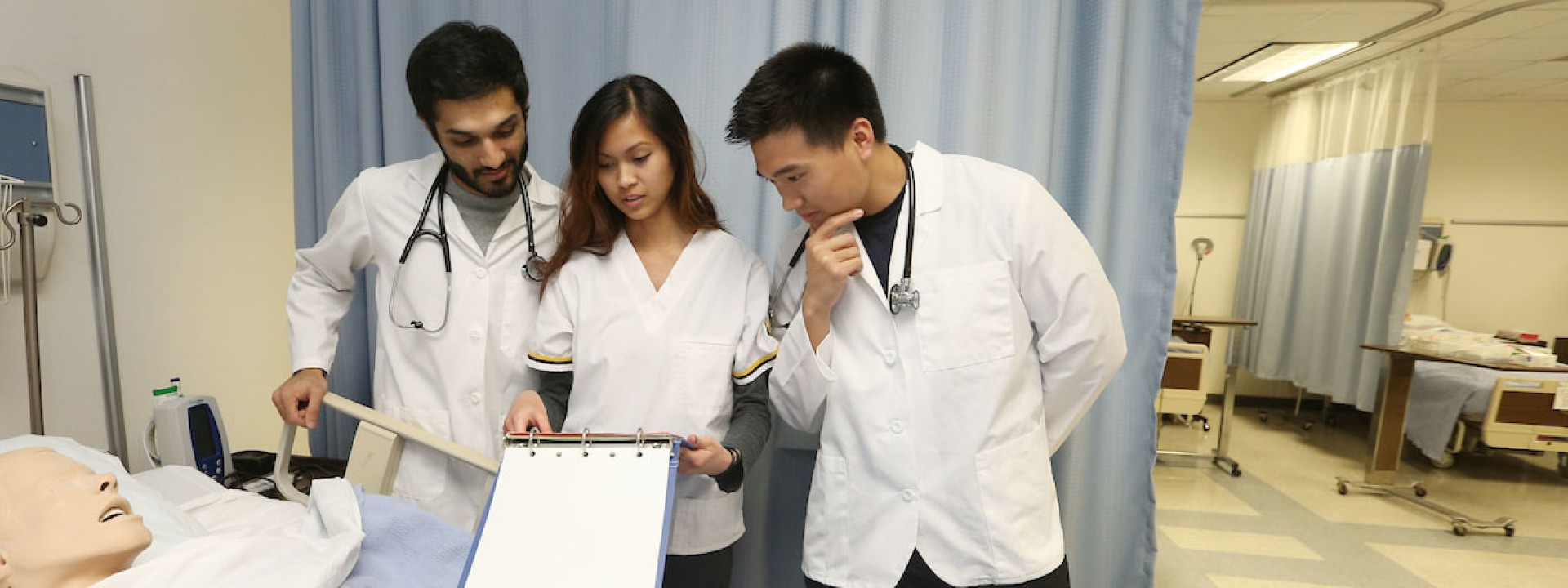 Image of three students in lab coats standing over an educational dummy.