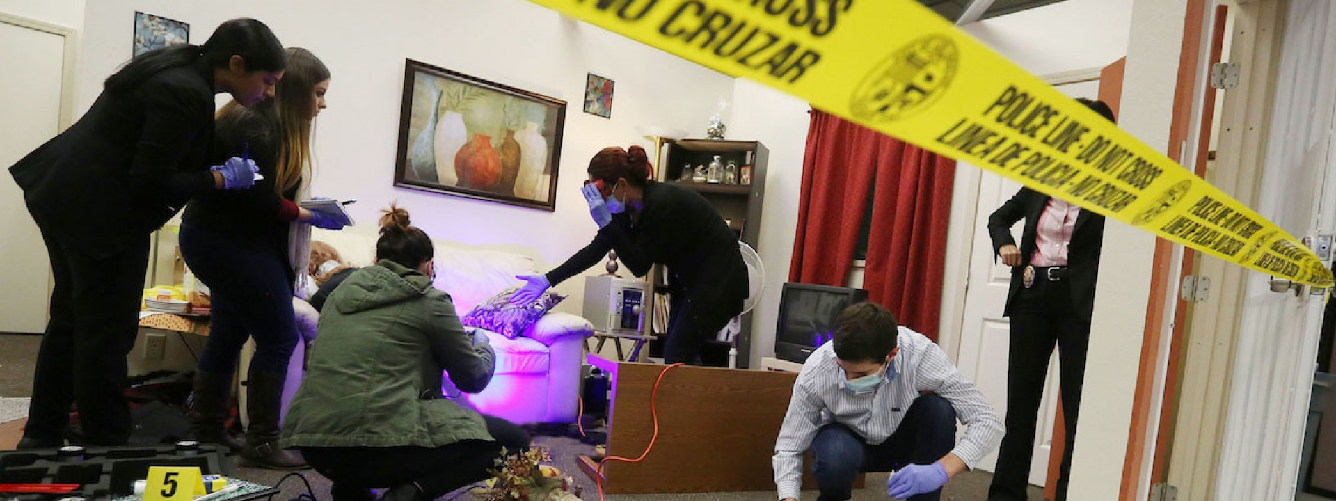 Image of a mock crime scene with caution tape and black lights, with forensic students investigating.