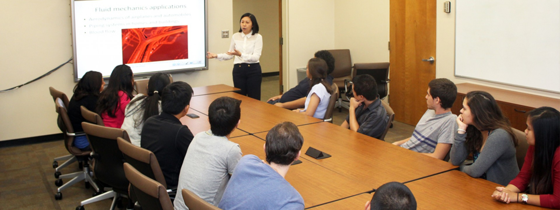 Group of Cal State LA students in a classroom around a conference table facing a projector screen as a lecturer teaches.