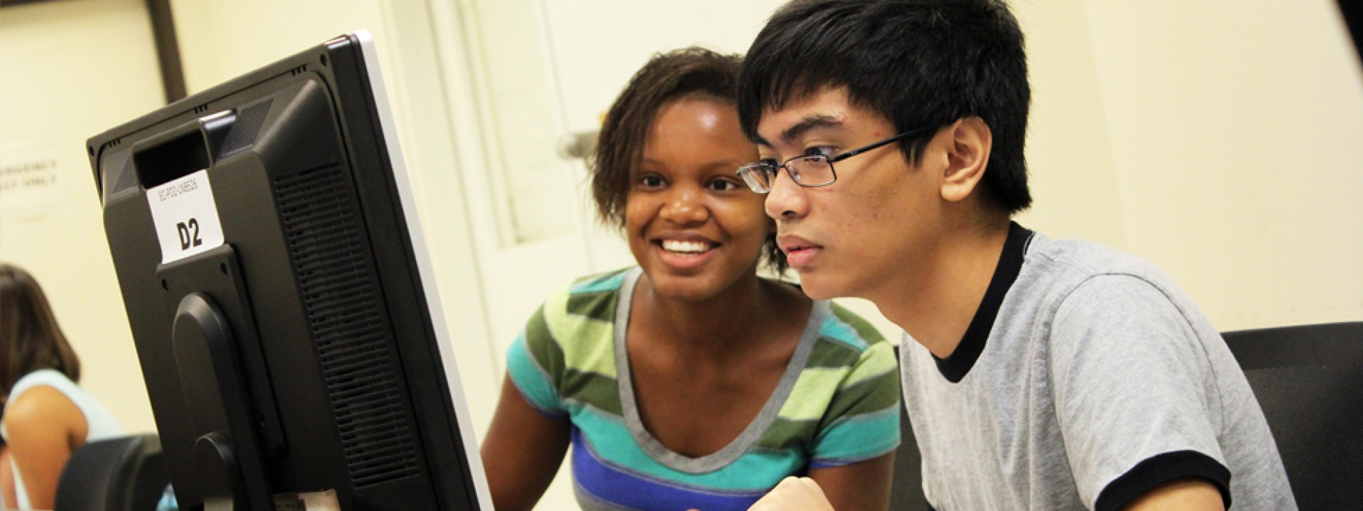Two Honors College students facing a computer screen intently.