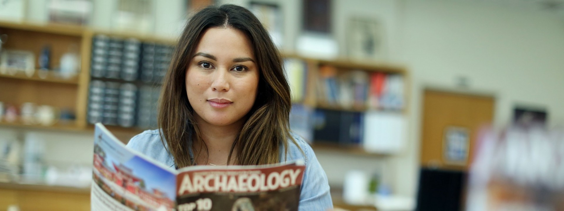 Image of a female student looking directly into the camera as she holds a copy of Archaeology Magazine in a classroom.