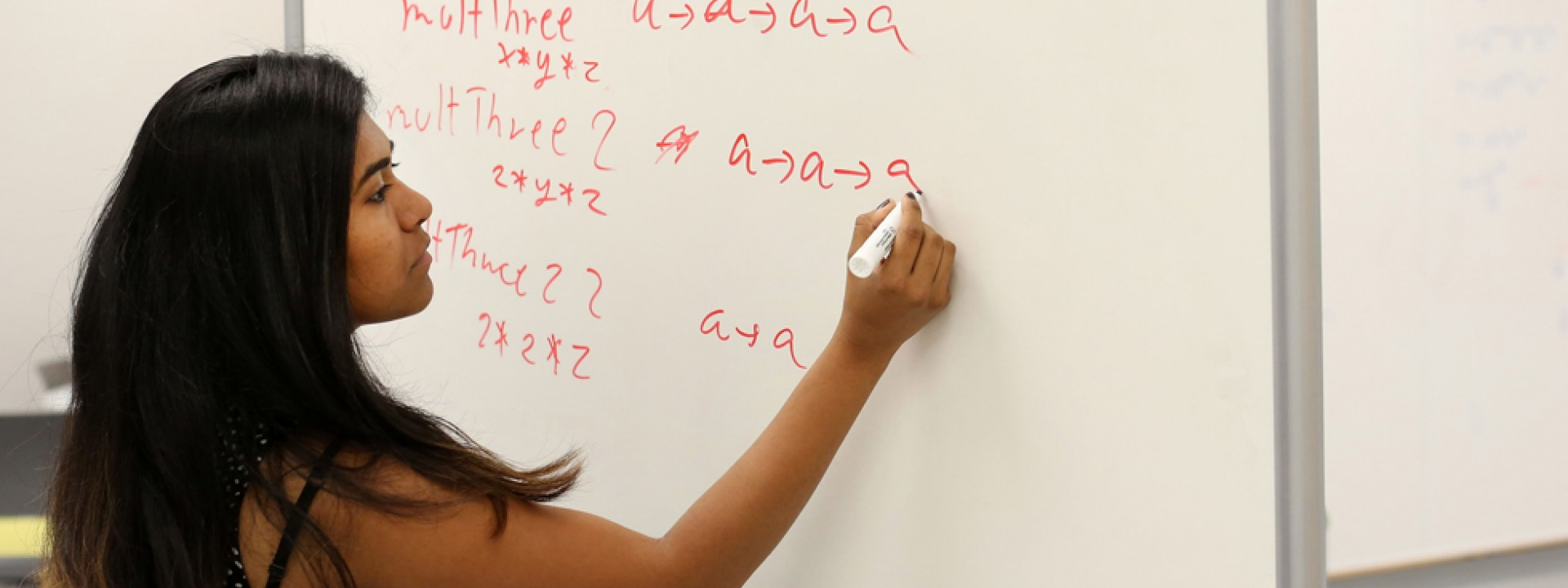 Image of a female student writing an equation on a dry erase board in red ink.