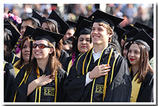 Students put their hands over their hearts to listen to the National Anthem during the 67th Commencement ceremony.