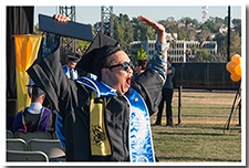 A student celebrates receiving his diploma at the 67th Commencement.