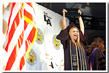 A student hoists her diploma in the air in celebration at the 67th Commencement.