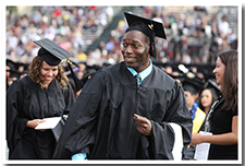 A master's candidate walks with his hood into the Cal State L.A. Athletics Stadium for the 67th Commencement ceremony.