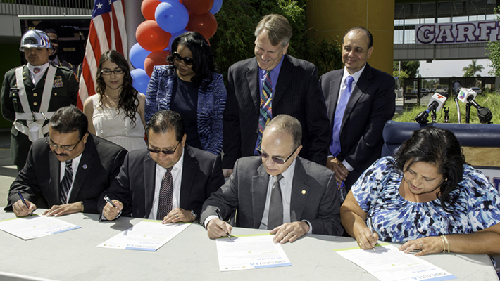 From left: Garfield High School Principal Jose Huerta, East Los Angeles College President Marvin Martinez, President Covino and LAUSD Board Member Monica Garcia sign their commitment to the GO East L.A. project.