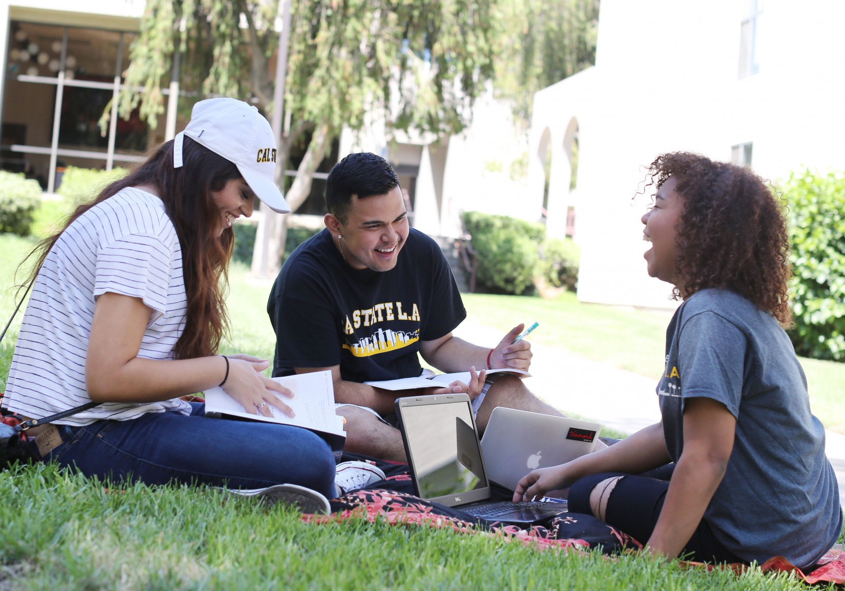 Three students sitting outdoors on a lawn, studying and smiling.