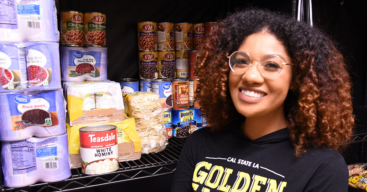 Student standing in front of shelves stocked with canned goods.