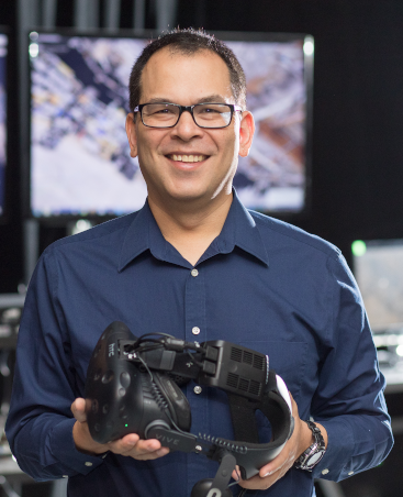 Image of David Krum, holding a virtual reality display.