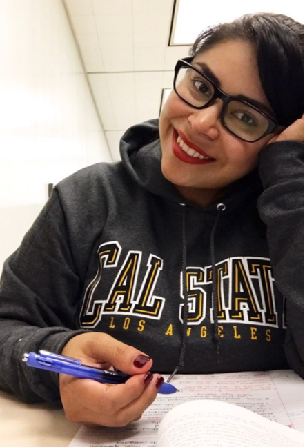 young lady with glasses wearing cal state Los angeles sweatshirt, smiling while studying in class.