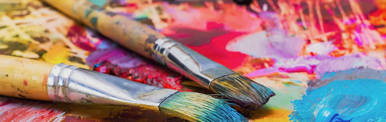 artist paint brushes laying on palate of bright paints